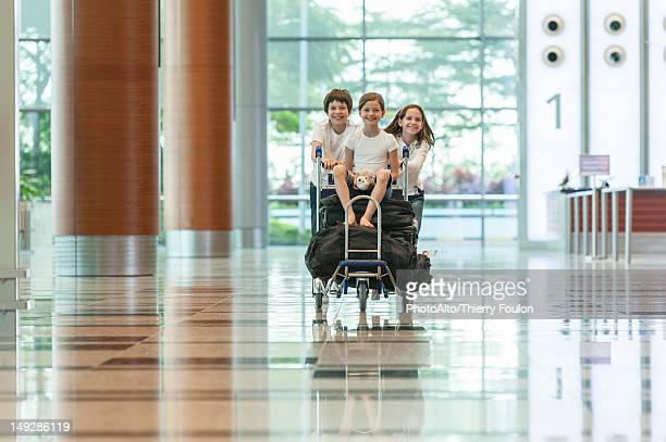 Brother and sister pushing younger sister on luggage cart in airport