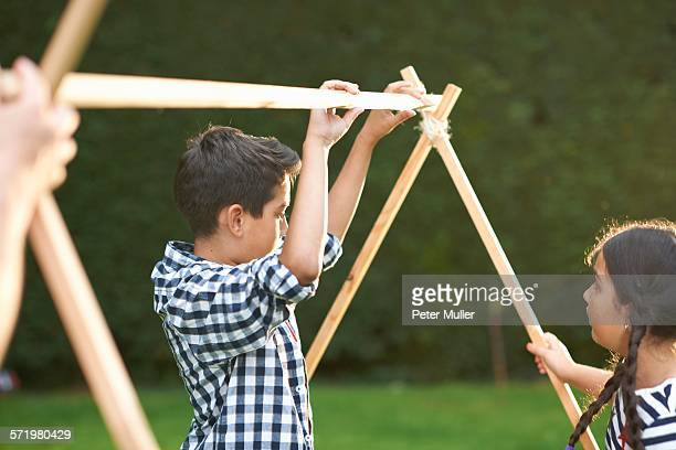 Brother and sister putting up homemade tent frame in garden