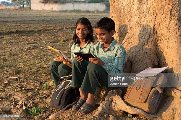 Brother and sister reading and using tablet device