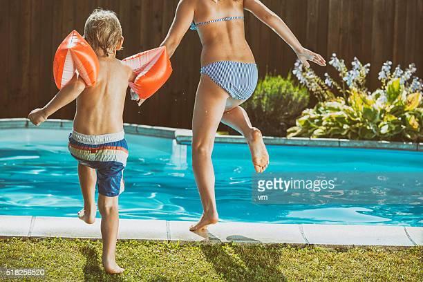 Bruder und Schwester Laufen und Springen in den Schwimmbad