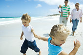 Brother and sister running and laughing on beach in front of parents with baby