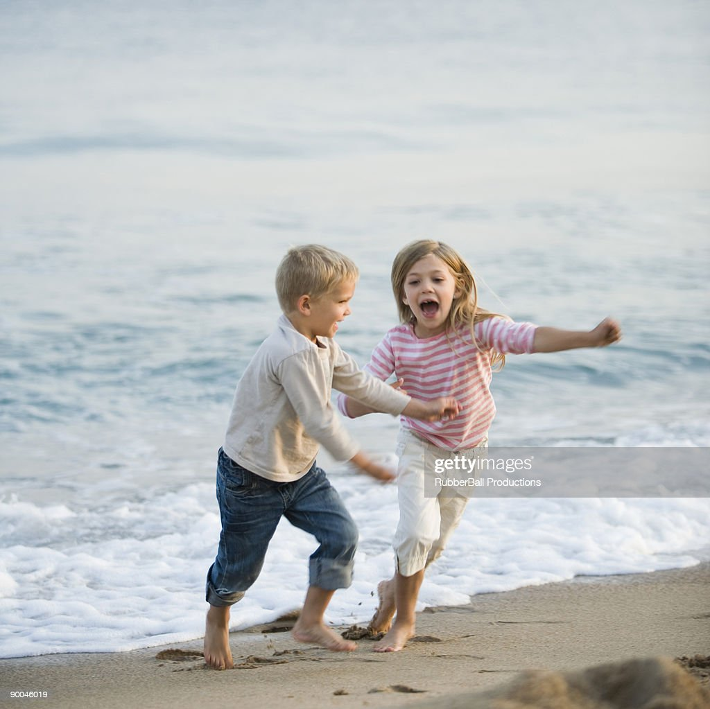 brother and sister running at the beach : Stock Photo