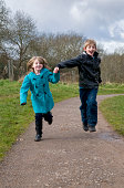 Brother and sister running hand in hand