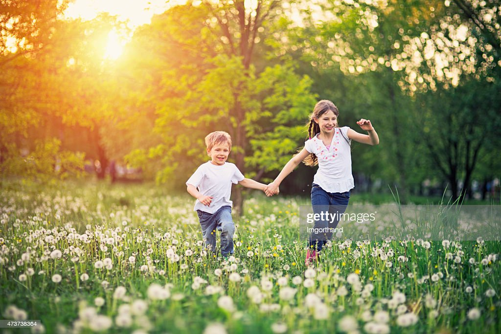 Brother and sister running in dandelion field. : Stock Photo