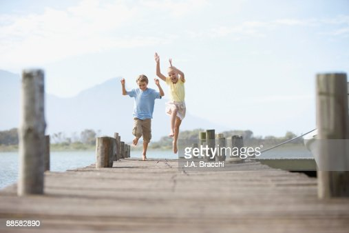 Brother and sister running on dock : Stock Photo