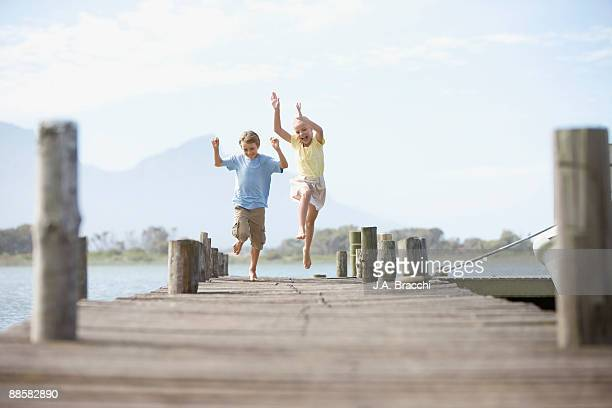 Brother and sister running on dock