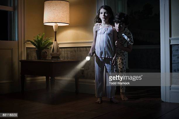 brother and sister searching with flashlight