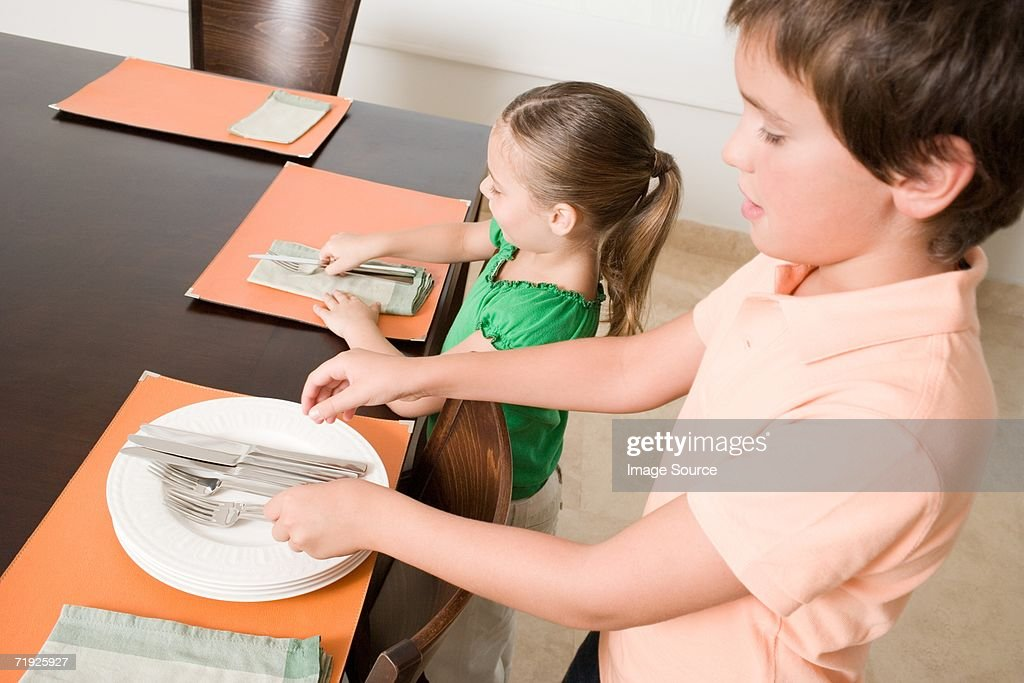 Brother and sister setting the table : Stock Photo