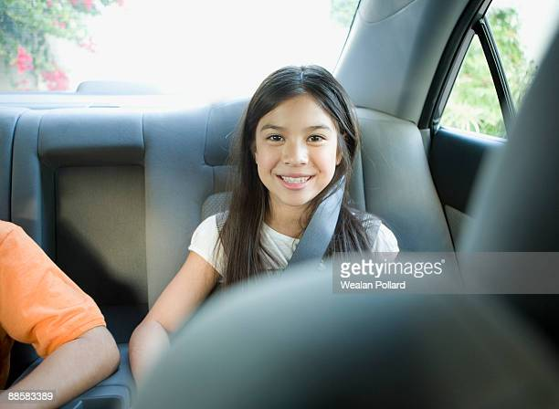 Brother and sister sitting in back seat of car