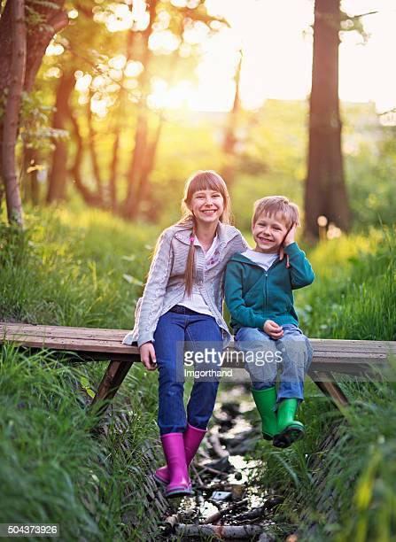 Hermano y hermana sentado en el puente en el bosque