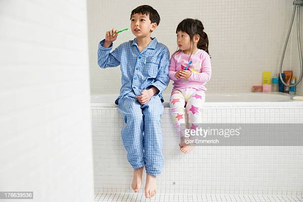 Brother and sister sitting on edge of bath with toothbrushes