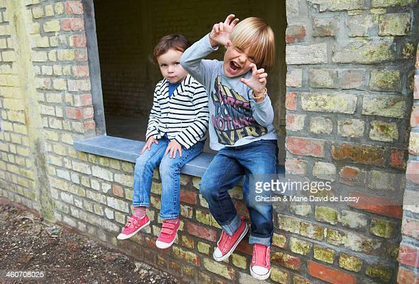 Brother and sister sitting on window sill