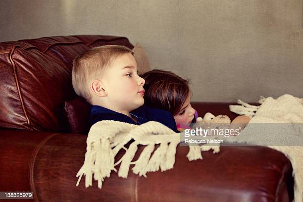 Brother and sister sitting together in arm chair