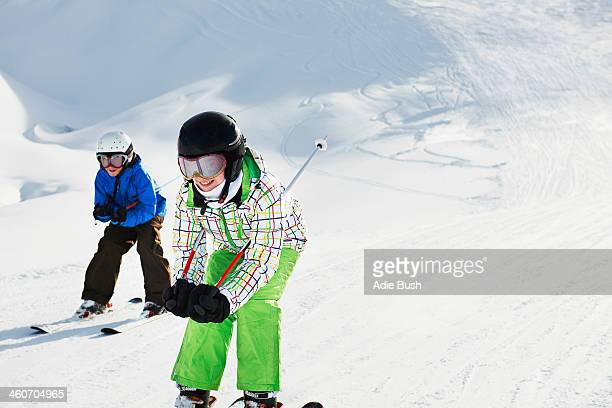 Brother and sister skiing downhill, Les Arcs, Haute-Savoie, France