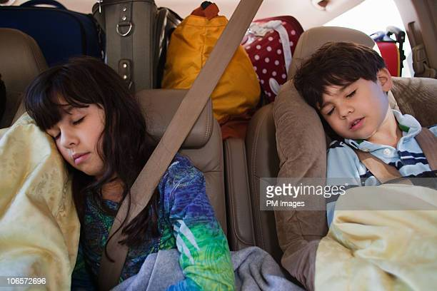 Brother and sister sleeping in car