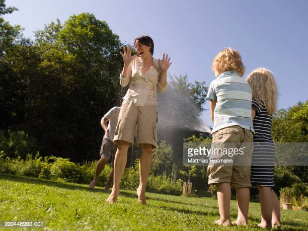 Brother and sister (3-5) spraying mother with hose in garden