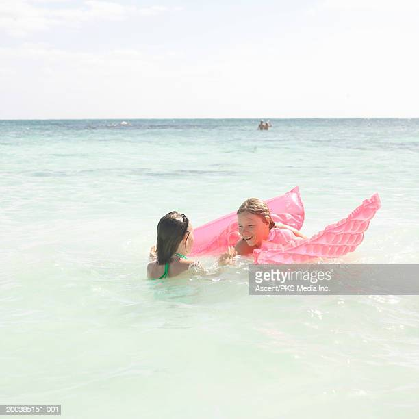 Brother and sister (10-13) swimming in ocean with inflatable raft