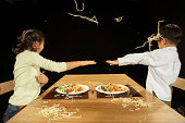 Brother and sister (4-10) throwing pasta at one another at table