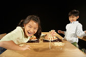 Brother and sister (4-10) throwing pasta at table, laughing