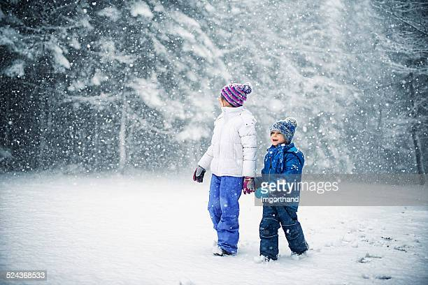 Brother and sister walking in amazing snow