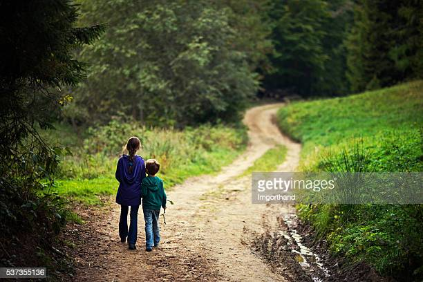 Brother and sister walking on a forest path