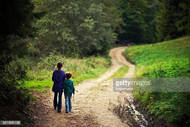 Hermano y hermana caminando en un bosque de ruta