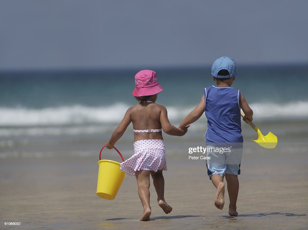 Brother and sister walking to sea