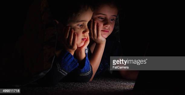 Brother and Sister Watching a Movie at Night