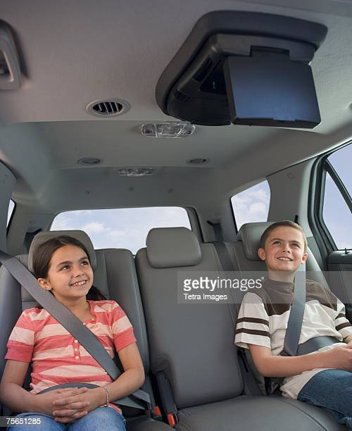 Brother and sister watching moving in car
