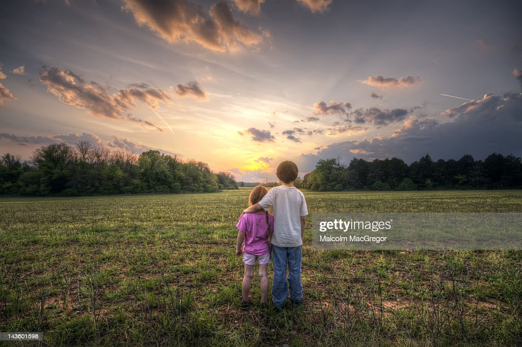 Brother and sister watching sunset