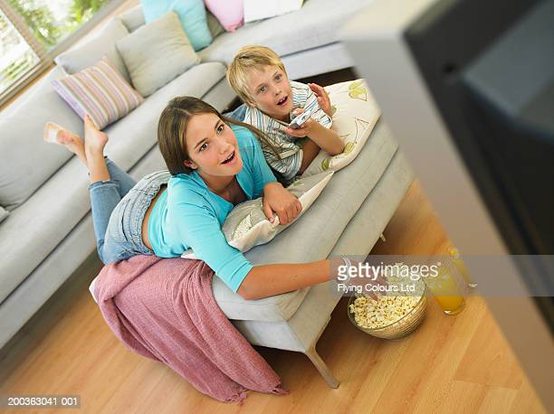 Brother (7-9) and sister (14-16) watching television