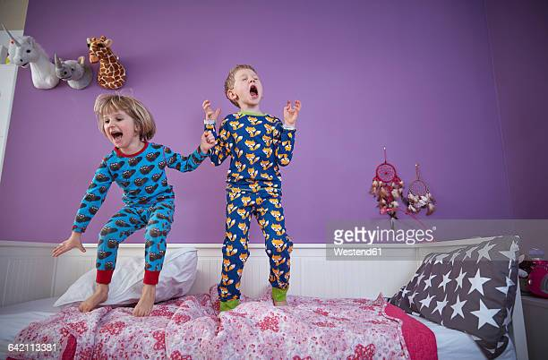 Brother and sister wearing pajamas romping around in childrens room