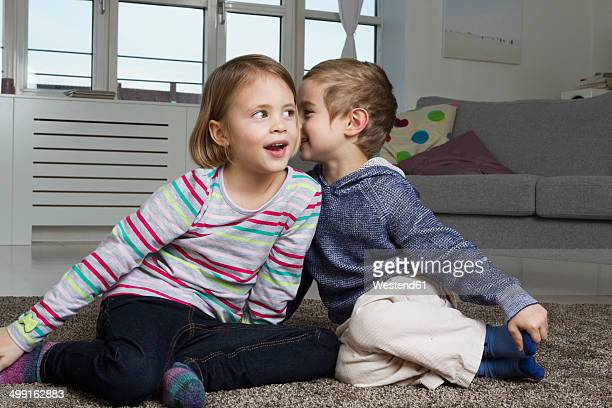 Brother and sister whispering on carpet in living room