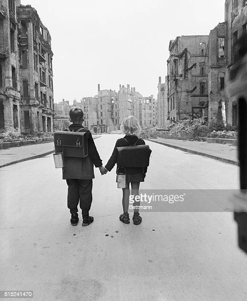A brother and sister who live in a bombedout section of Berlin walk down a deserted street on their way home from school The mess utensils made from...