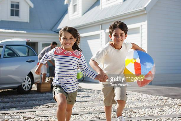 兄と妹のビーチボールランニングでのドライブウェイ
