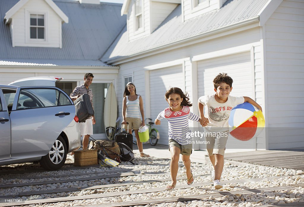 Brother and sister with beach ball running on driveway : Stock Photo