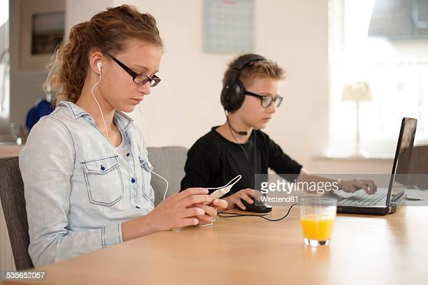 Brother and sister with headphones and earphones using laptop and smartphone