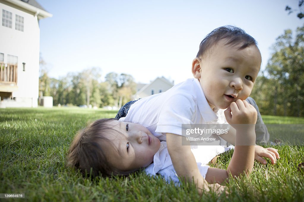 Brother and sister wrestling in the grass : Stock Photo