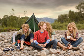 Brother and sisters playing outdoors around small pup tent along a creek