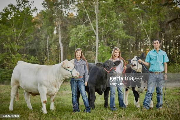 Brother and sisters posing with cows in field
