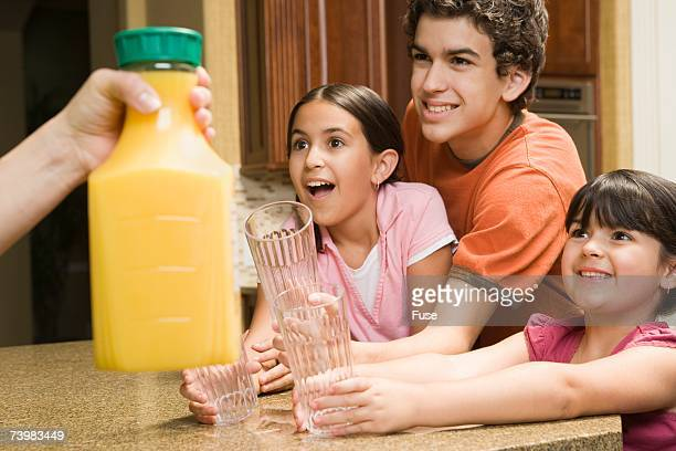 Brother and sisters with a bottle of orange juice
