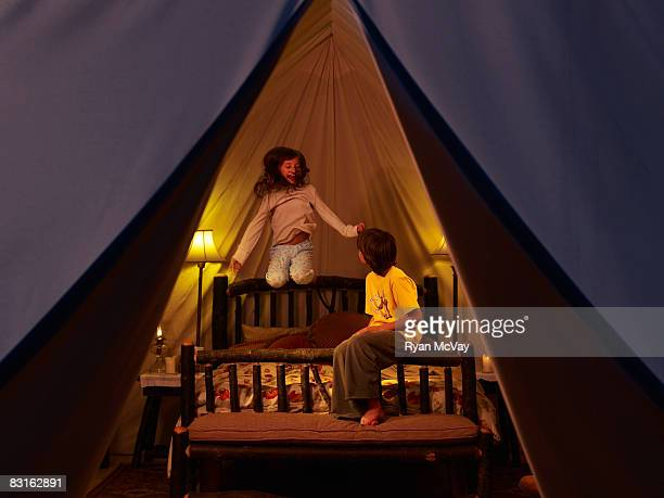 Brother and siter playing on bed inside tent.