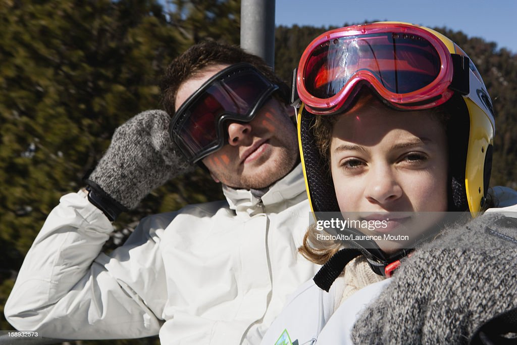 Brother and younger sister on chair lift, portrait : Stock Photo