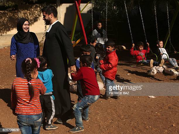 Brother Andres a Mexican cleric with the Brothers of the Christian Schools chats with a Muslim teacher as they play with refugee children from Syria...