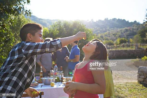 Brother feeding sister with grapes