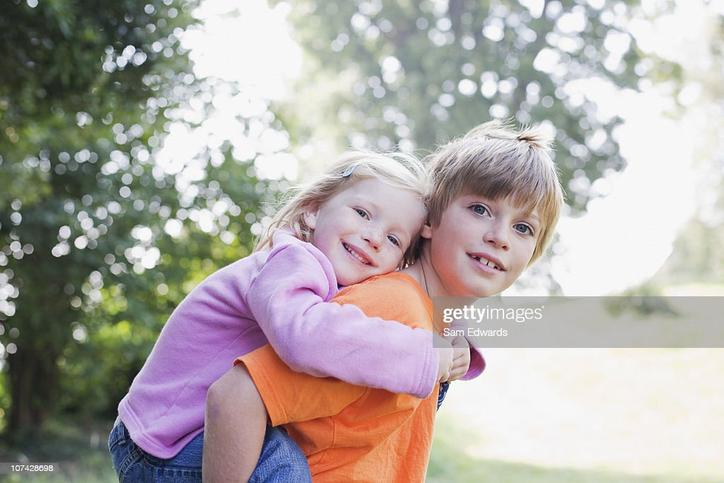 Brother giving sister piggyback ride : Stock Photo