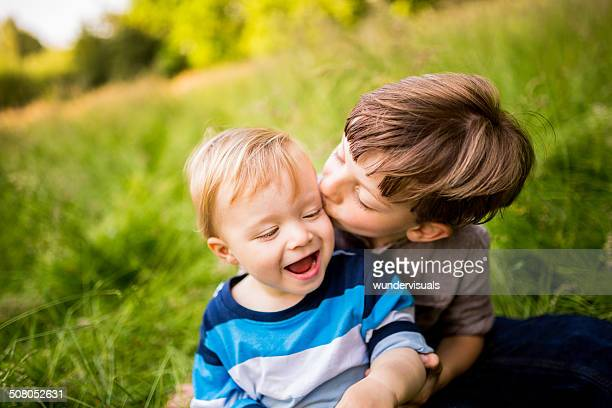 Brother kissing sibling on Cheek