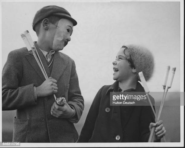 A brother makes his sister laugh with his mask Both of them hold fireworks for Guy Fawkes Day