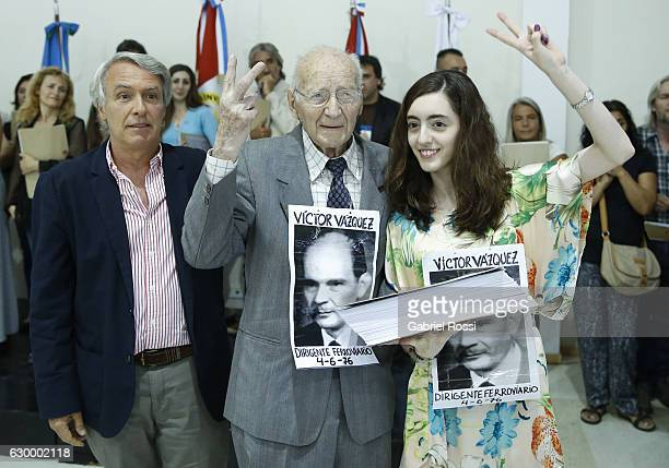 Brother of disappeared railway worker Victor Vazquez and his greatgranddaughter gesture during the delivery of repaired files to the descendants of...