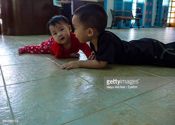 Brother Playing With Toddler While Lying On Floor